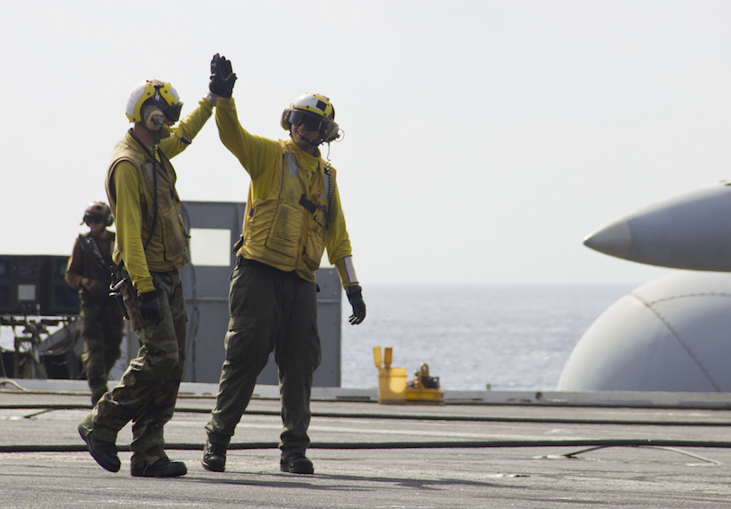 Sailors high-five after aircraft launches. US Navy photo by Mass Communication Specialist Seaman Michelle N. Rasmusson/Released