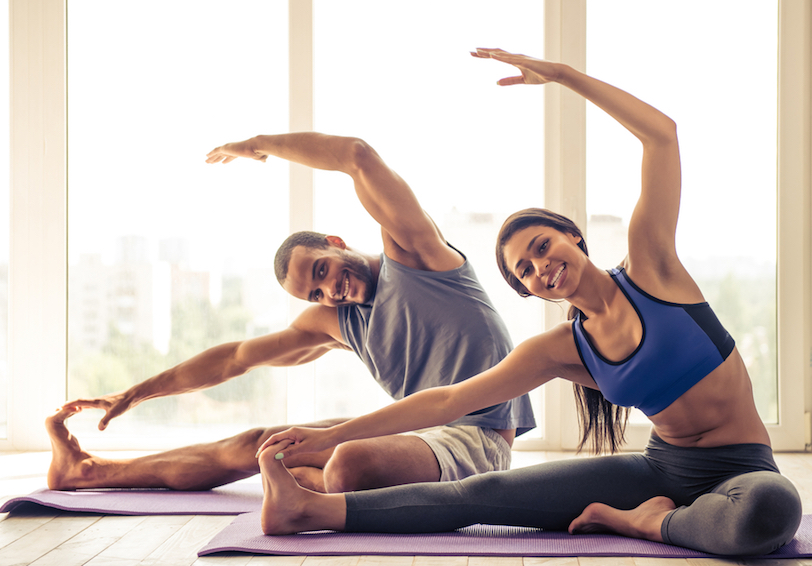 Couple stretching on yoga mats