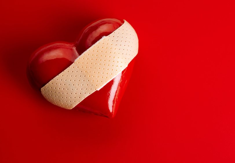 Bandage affixed to a red heart on red background