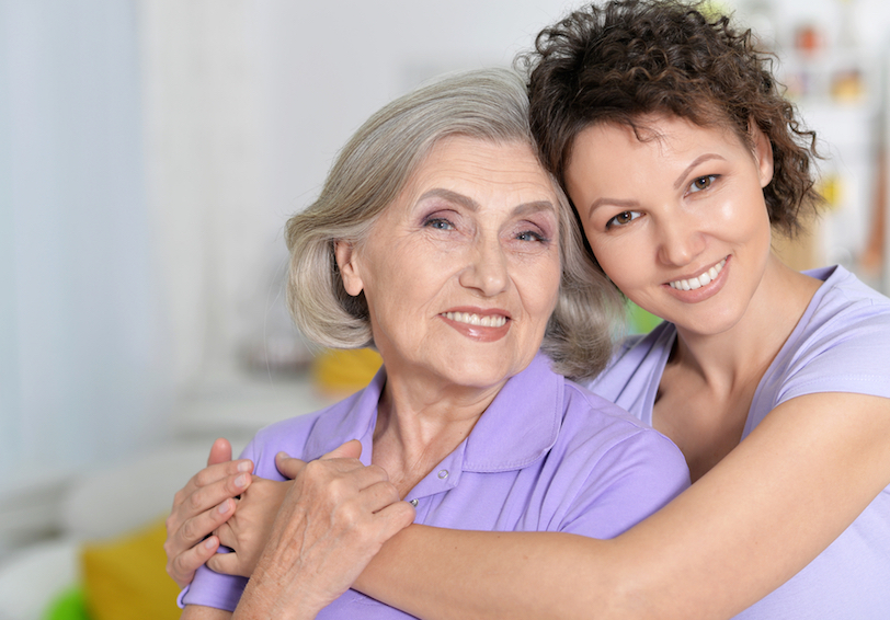 Woman and older woman smiling at the camera with arms around each other