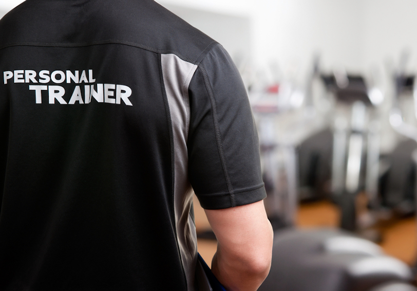 "Back of man wearing a shirt with words ""Personal Trainer"" looking out at gym"