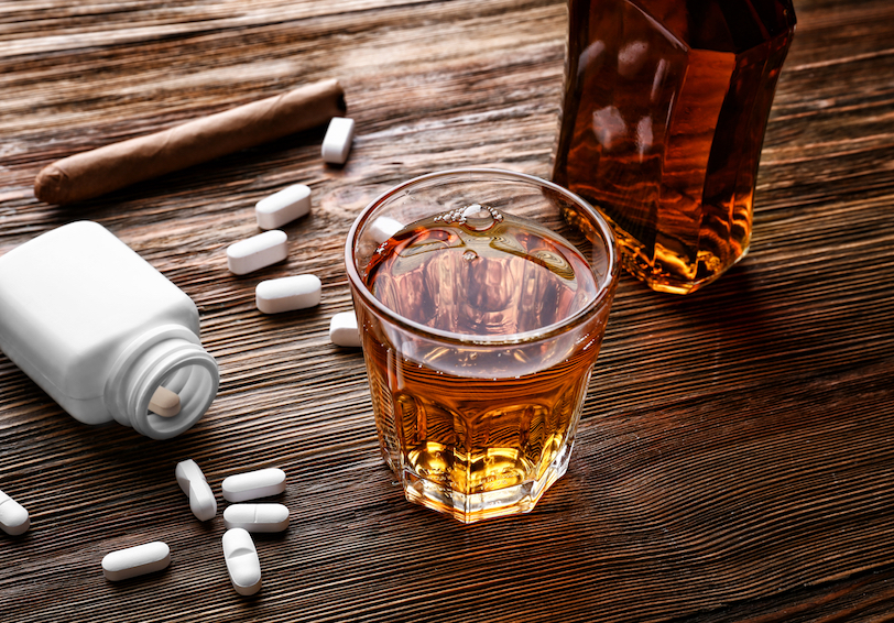 Pill bottle, pills, cigar, and liquor on wooden surface