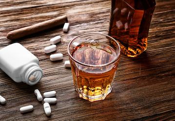 Pill bottle  pills  cigar  and liquor
