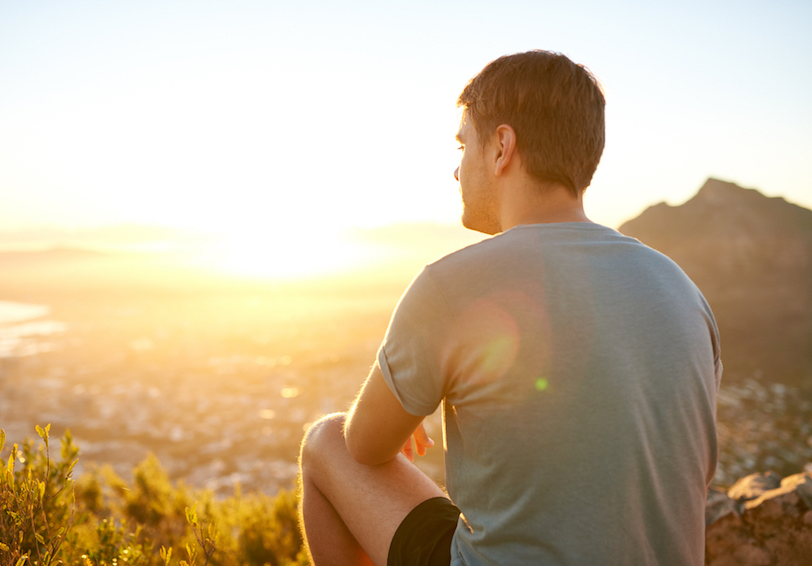 Man sitting on hill overlooking city watching a sunrise