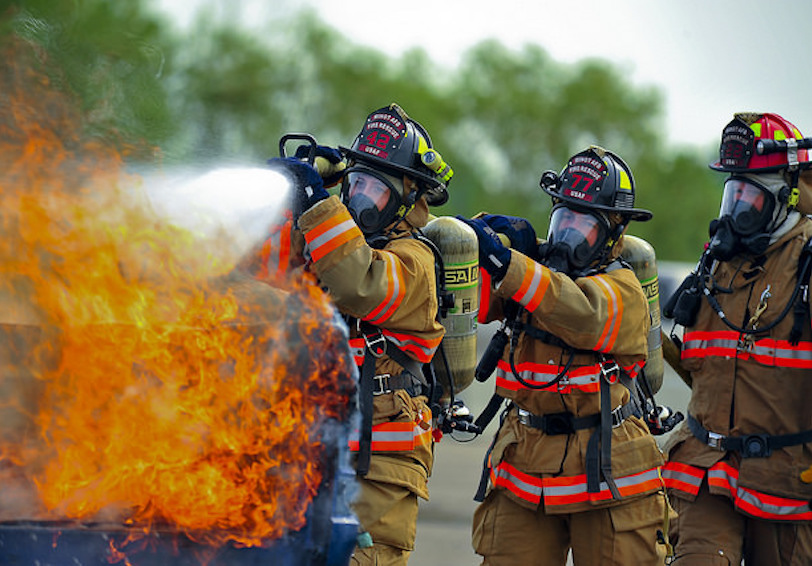 Team of firefighters with fire hose putting out a fire (U.S. Air Force photo by Senior Airman Brittany Y. Bateman/Released)