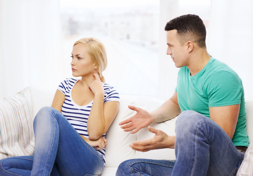 Man and woman sitting on couch. Man is holding hands out as if explaining something and woman is looking away irritated.