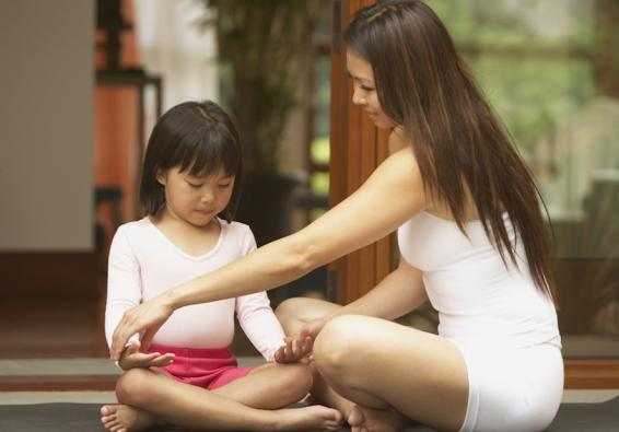 Mother teaching little girl to meditate