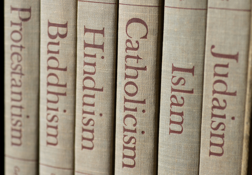 Spines of books reading: Protestantism, Buddhism, Hinduism, Catholicism, Islam, and Judaism