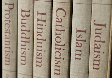 Spines of books reading  Protestantism  Buddhism  Hinduism  Catholicism  Islam  and Judaism