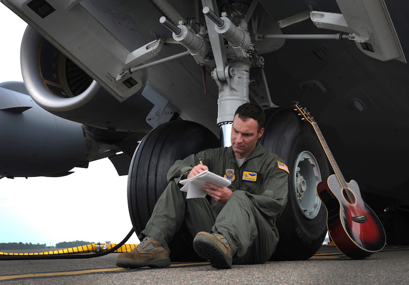 Major Pete Reddan writes a song while leaning on the front tires of a C-17 Globemaster III (U.S. Air Force photo by Airman 1st Class Ashlee Galloway)