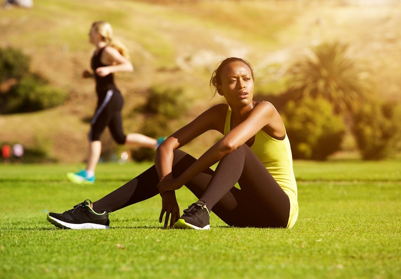 Woman in workout clothing sitting in grassy area catching her breath
