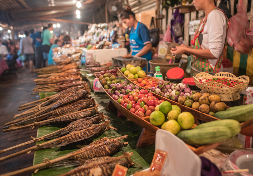 Street booth food in Luang Prabang, Laos including fruits, vegetables and cooked meats