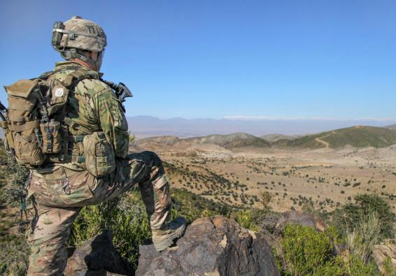 Soldier looking down into valley. U.S. Army photo by Sgt. 1st Class Abram Pinnington/Released