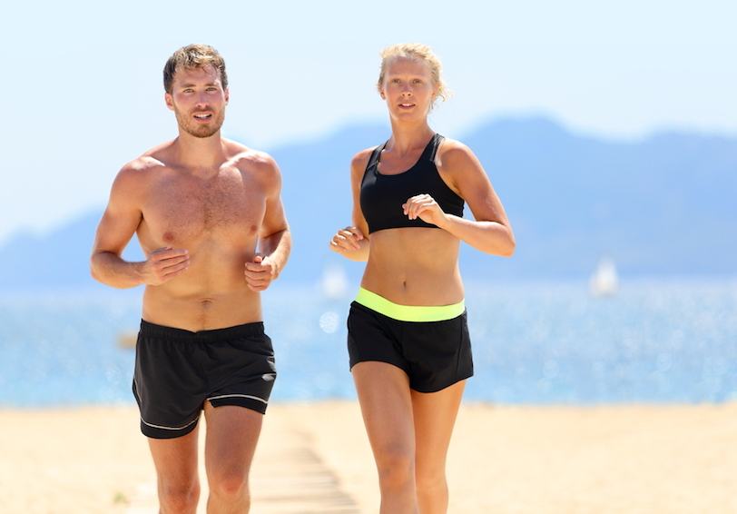 Man and woman running on beach on sunny day