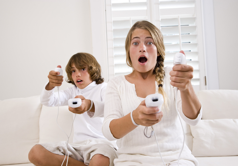 Boy and girl looking surprised while holding video game controllers