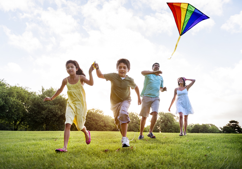 Little boy and girl flying a kite with their parents