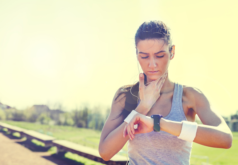 Woman in athletic clothes looking at watch and touching her neck to check pulse