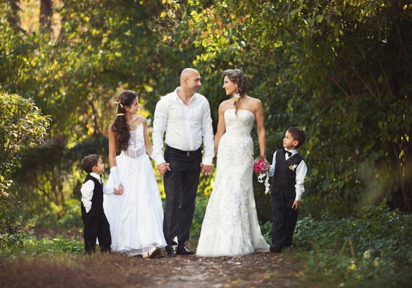Bride and groom holding hands with daughter and two small sons on path in wooded area