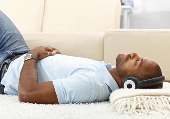 Man lying on floor wearing headphones