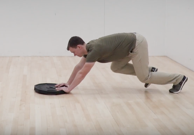 Man pushing weight across smooth floor
