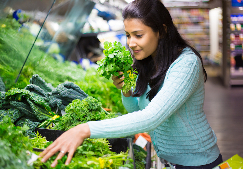 Woman examining leafy greens at grocery store