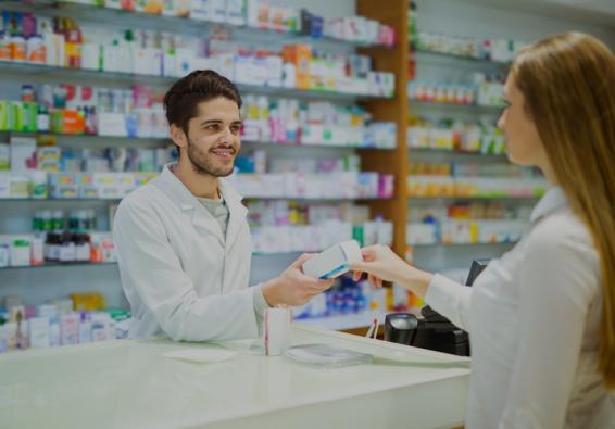 Woman handing prescription drug to pharmacist