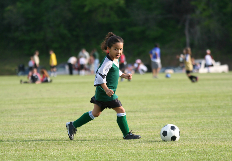 Young girl in soccer uniform kicking ball on a grassy area