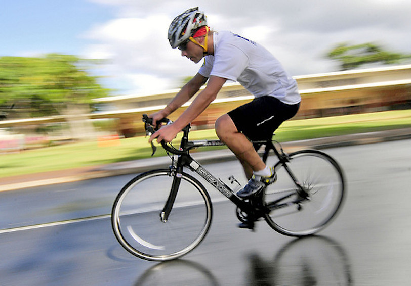 Man riding bicycle wearing helmet. Background is blurred.