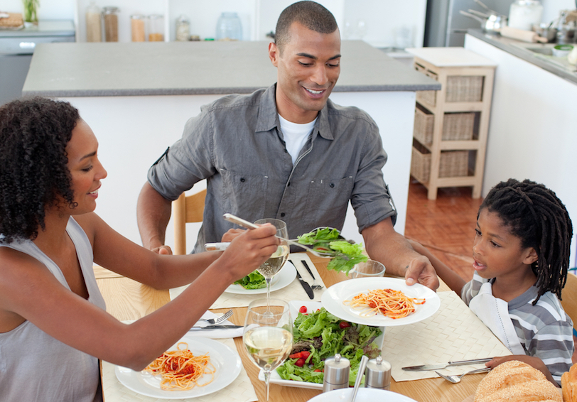Family eating spaghetti and salad on white plates