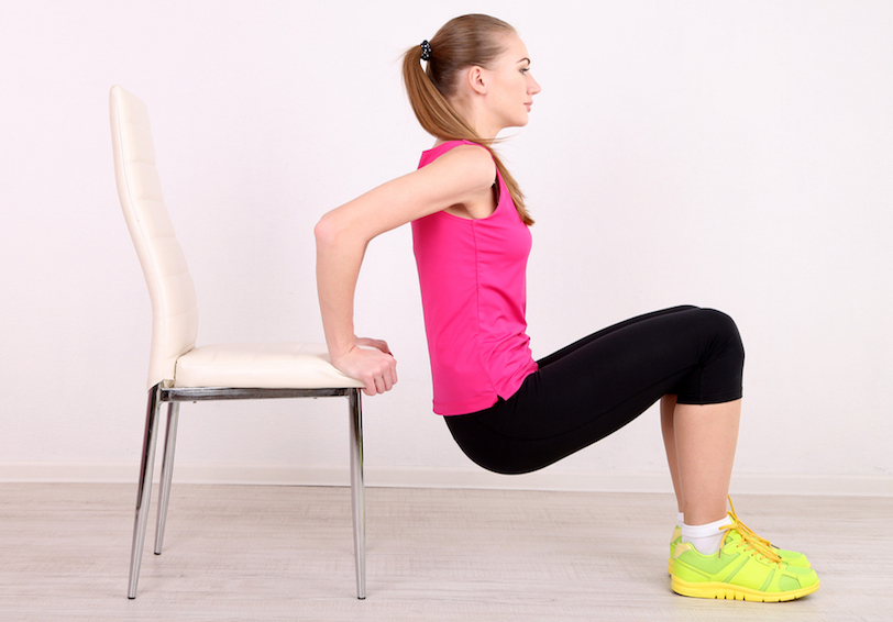 Woman doing tricep dips using a chair