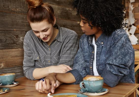 Lesbian couple holding hands and talking at a cafe table