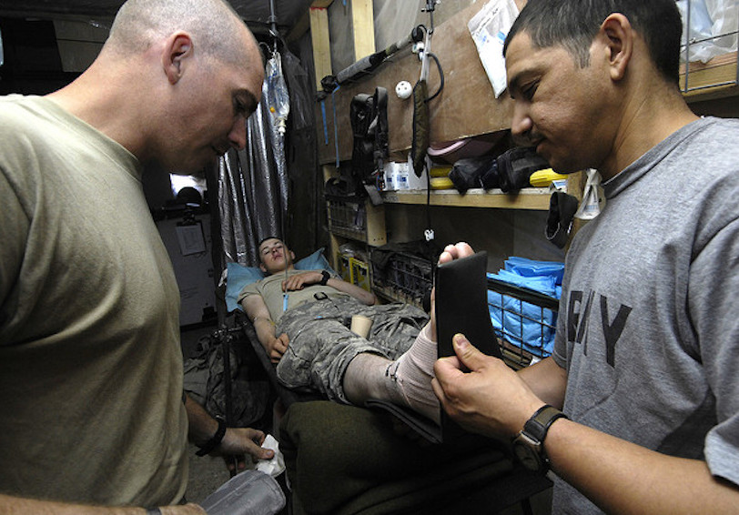 Two soldiers stabilizing injured ankle for another soldier (U.S. Air Force photo by Master Sgt. Jonathan Doti)