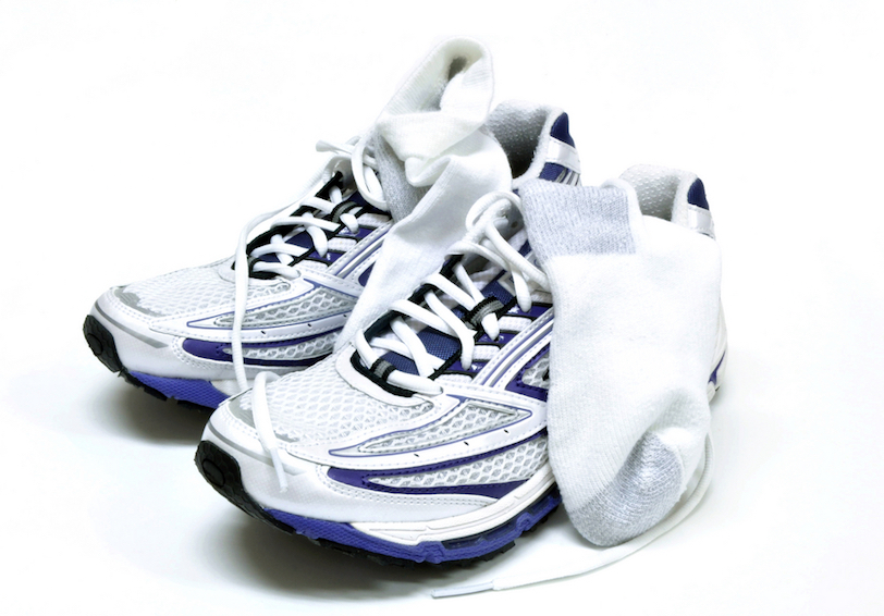 White running shoes with socks laid over side of shoe white background