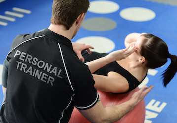 Personal trainer helping woman with exercise form
