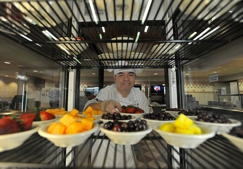 Airman restocks the dessert fridge with fruit. (U.S. Air Force photo by Senior Airman Xavier Navarro/Released)