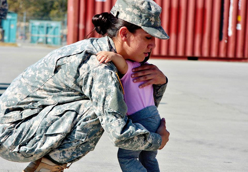 Female soldier bending down to hug her small child (U.S. Army photo by Maj. Johnpaul Arnold)