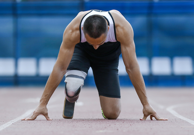 Man with prosthetic leg in start position getting ready to run on track
