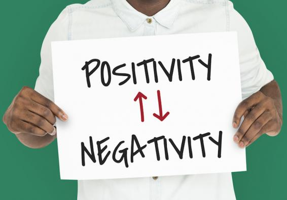 "Man holding a sign with the words ""Positivity"" and ""Negativity"" with arrows between"