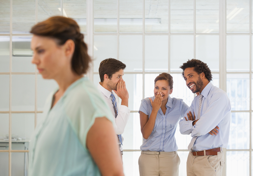 Group of coworkers laughing at a woman behind her back