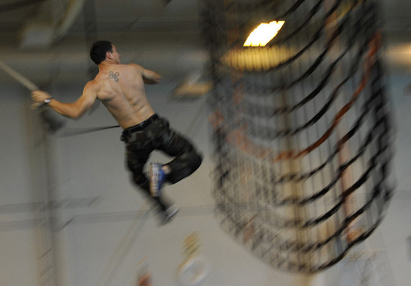 U.S. Navy SEAL candidate swings to an cargo net (U.S. Navy Photo by Mass Communication Specialist 1st Class Les Long/Released)