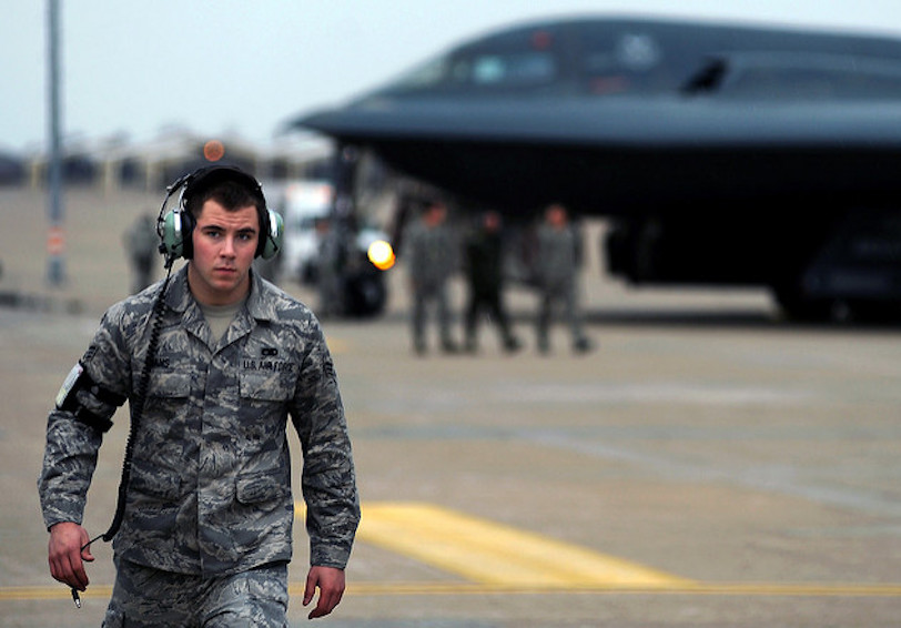 Airman walking away from plane wearing hearing protection (US Air Force/Kenny Holston)
