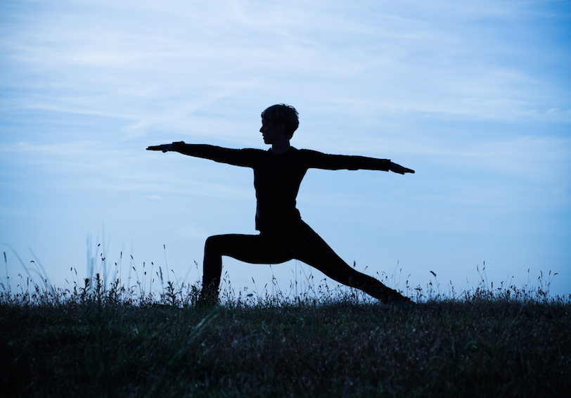 Silhouette of person in Warrior II yoga position