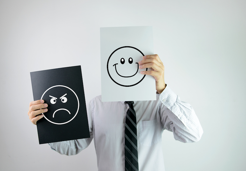 Man holding paper in front of his face with happy face and another piece of paper with an angry face off to the side