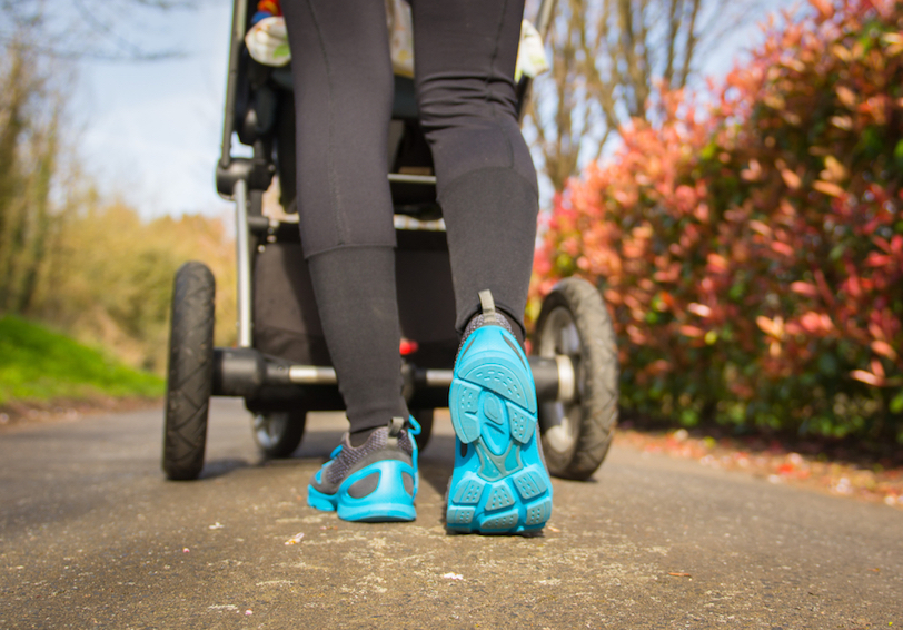 Legs of woman with athletic pants and running shoes pushing stroller