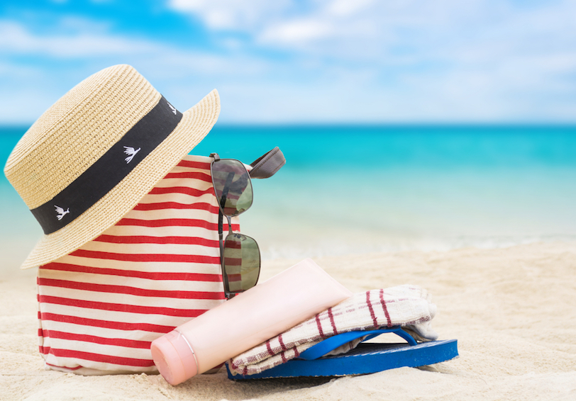 Hat, beach bag, sunglasses, sunscreen bottle, and sandals sitting on sandy beach