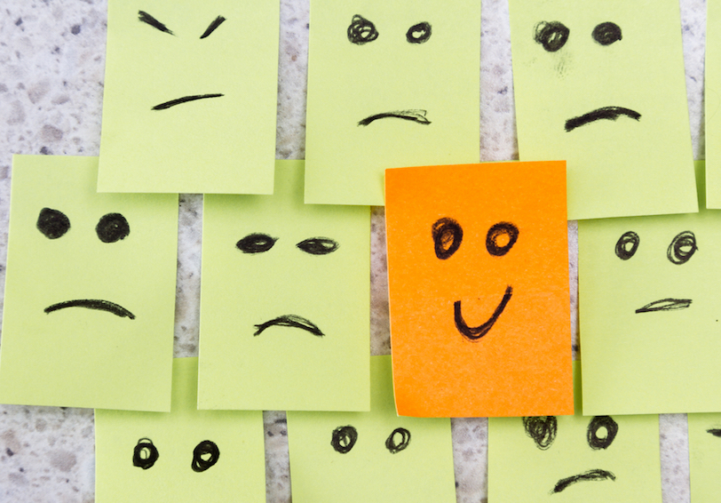 One orange post-it with happy face drawn on it in the middle of many yellow post-its with sad or mad faces on them