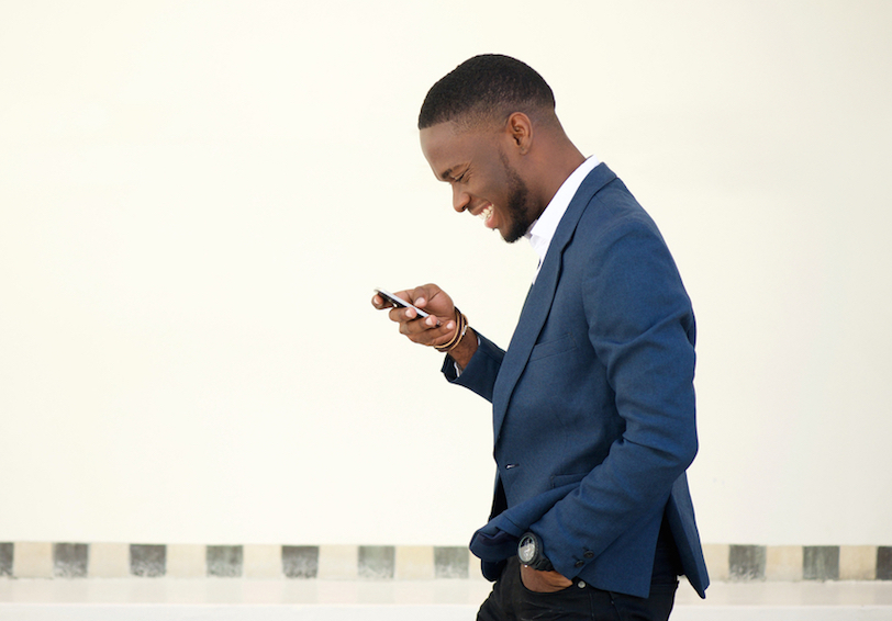 Man in suit walking and looking down at cell phone