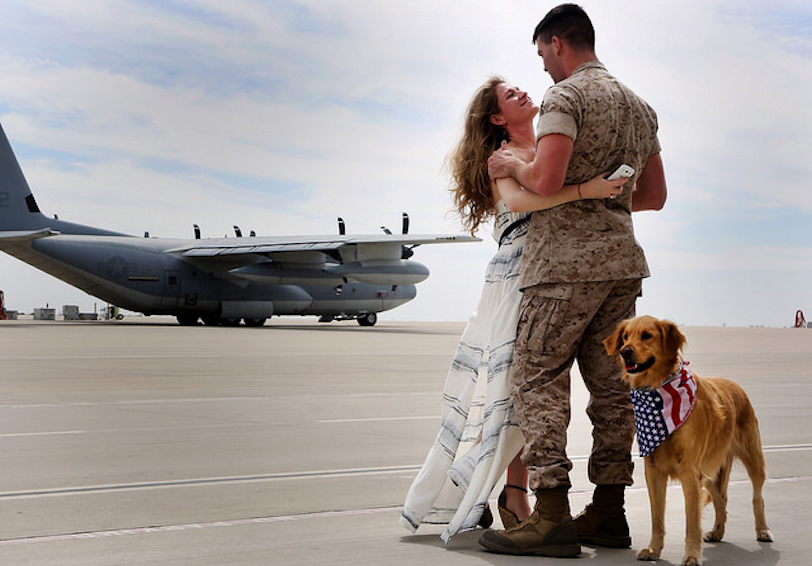 Marine and his spouse hugging with dog standing nearby (U.S. Marine Corps photo by Sgt. Keonaona C. Paulo/ Released)