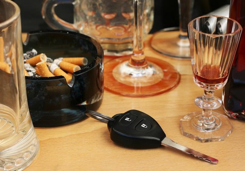 Full ashtray, empty alcohol glasses, car key