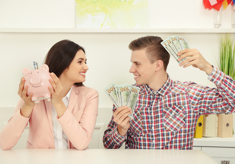 Smiling couple holding piggy bank and money